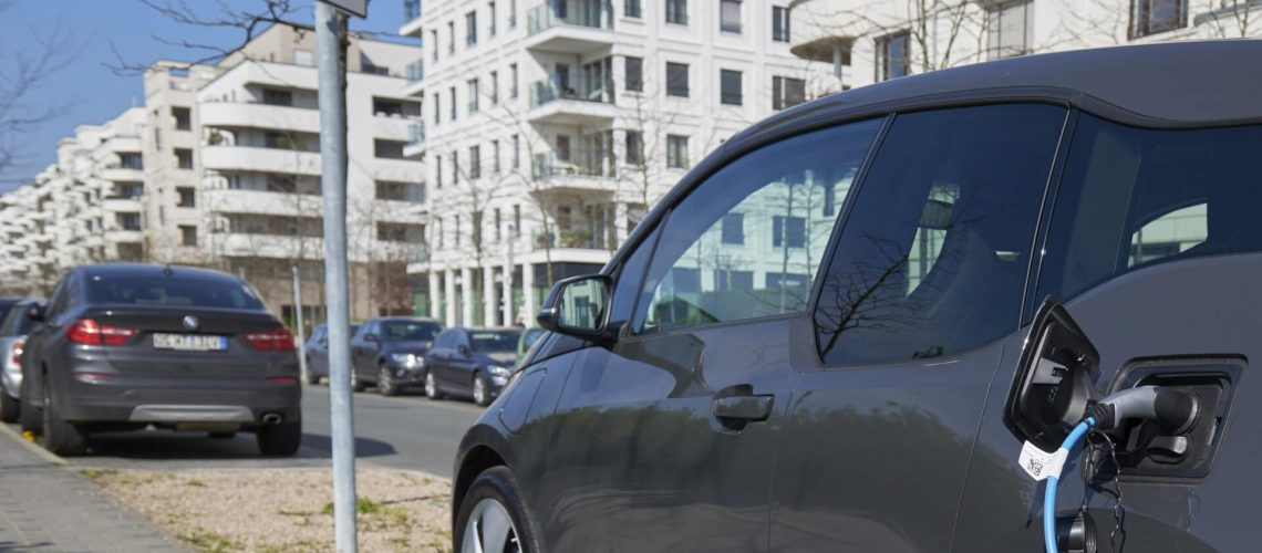 Duesseldorf, Germany- April 10, 2019: A dark gray BMW i3 is parked beside the street and is connected with a blue power chord to a recharging station. In the background the new apartment houses of the Duesseldorf quarter